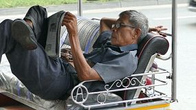 A Thai tuk tuk driver takes a break from driver to read his daily newspaper in the streets of Bangkok, Thailand.