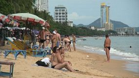 A group of large European sunbathers enjoy their vacation on the beach in Pattaya, Thailand.
