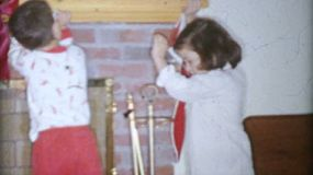 Three excited little kids hang their Christmas stockings by the fireplace on Christmas Day in 1963.