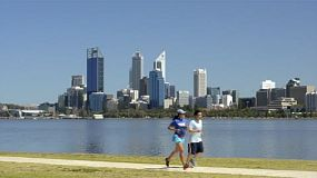 People exercising along the swan river, running, walking, and cycling, with perth city in the background.