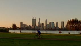 Various people passing by as they exercise along the South Perth Foreshore, with a view of the Swan River and city skyline in the background.