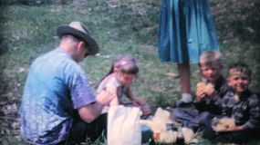 A family enjoys a picnic and spending time together during summer holidays in 1964.