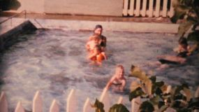 A young family enjoys spending time in the campground swimming pool while on holidays in the summer of 1964.