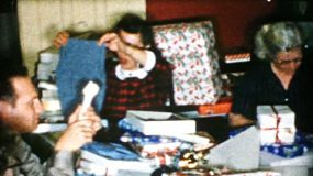 Family members enjoying spending time together and opening presents on Christmas morning in 1956.