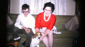 A loving family spend time posing with their new puppy at Christmas in 1961.