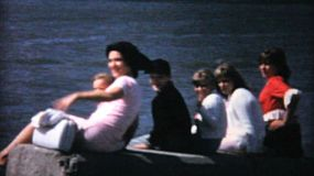 A family spends time together at the ocean watching a big ship sail past in 1967.