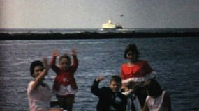 A family spends time together at the ocean watching a big ship sail past in 1964.