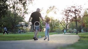 A proud father and his eight year old daughter enjoy a walk in the park on a beautiful summer day.