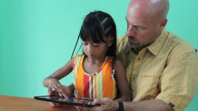 A father plays games on his digital tablet with his cute 7 year old Asian daughter.