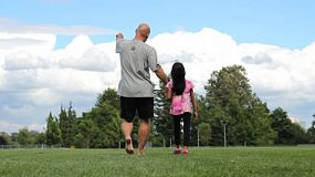 A proud father and his seven year old daughter enjoy a walk in the field on a beautiful summer day.