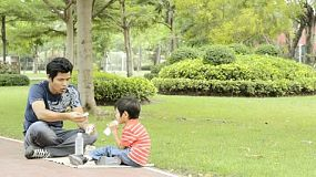An Asian father and son having a picnic in a park.