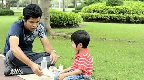 An Asian father and son enjoying a picnic together in a park.