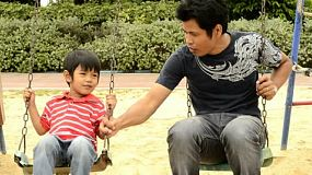 An Asian father and son playing together on a swing set.