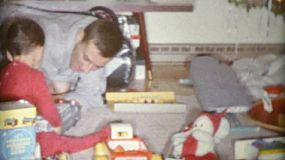 A father and son spend time playing with Christmas gifts together in 1963.