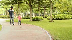 An Asian father points something out while walking in the park with his son.