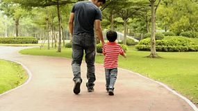 An Asian father and son walking together in a park.