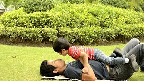 An Asian father kisses his son while playing together on the grass in a park.