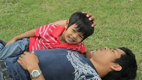 A loving father spends some time cuddling with his cute Asian son at the park.