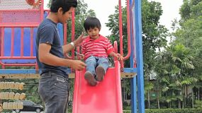 A father helps his cute Asian son down the slide at the playground in the park.