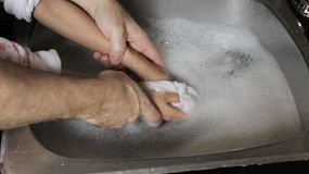 A father lovingly washes his 6 year old daughters hands in soapy water in the sink.