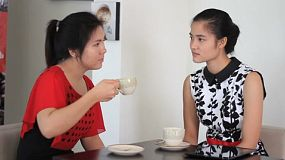 A good friend comforts her friend while they chat over coffee in a cafe in Bangkok, Thailand.