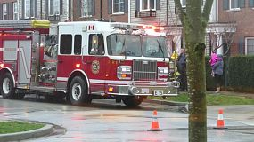 A first responder firetruck arrives in the pouring rain at the scene of a crisis in the suburbs.