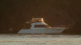 The late afternoon sun shining on a boat moored on the Swan River in Perth, Western Australia.