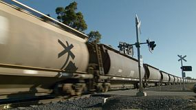 Carriages on a long freight train passing by a railway crossing in Western Australia.