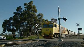 A long freight train passing by a railway crossing in Western Australia.