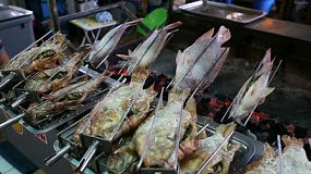 Incredibly delicious fresh fish cook on the rotisserie over an open flame on the streets of Bangkok, Thailand.