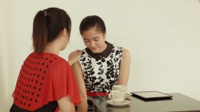 Two young Asian women praying for each other, while enjoying a cup of tea in a cafe.