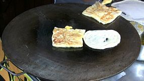 A woman fries roti bread on a large skillet at a local market in Bangkok, Thailand.
