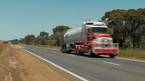A fuel tanker truck travelling down a highway in country Australia.
