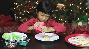 A cute little seven year old Asian girl enjoys making beautiful Christmas cookies in time for the holiday season.