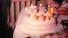 A cute little girl celebrates her 10th birthday by blowing out her candles at her party and cutting the cake in 1964.