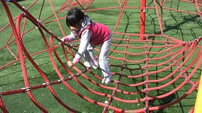 "A cute Asia girl successfully climbs a large ""spider web"" at the playground."