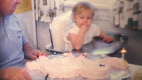 A cute little girl celebrates her 1st birthday by enjoying some delicious cake in 1970.