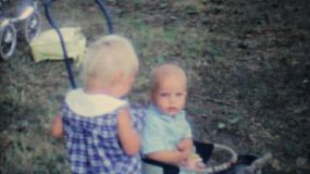 A cute blonde girl fusses over her baby sister at a family summer picnic in 1962.