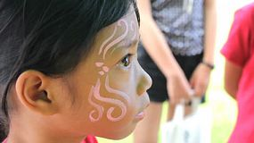 A cute little 7 year old Asian girl gets a pretty face painting design done on her face.