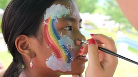 A cute 11 year old Asian girl gets clouds added to her rainbow face painting design.