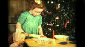 A cute little red headed girl makes a delicious pie for Christmas under the careful supervision of her dolly friend.
