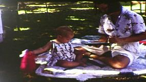 Young mother helping her one-year-old girl open birthday presents at her first birthday party, in Australia in September 1983.