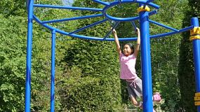 A cute little 9 year old Asian girl enjoys the challenge of climbing on the monkey bars at the playground.