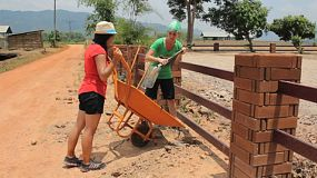 A pair of young adult girls working hard on a landscape project overseas in Thailand during a Christian missions trip.