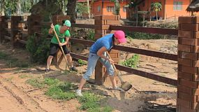 A bunch of foreign young adult girls work hard on a landscaping project overseas in Thailand on a missions trip.