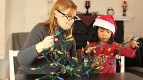 A mother and daughter have fun together trying to untangle the Christmas lights in preparation for trimming the tree.