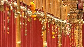 A row of small gold temple bells wave in the gentle breeze at a temple in Chiang Mai, Thailand.