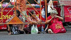 Three elderly Asian ladies decide to secure good seats for the Chinese New Year parade early before all the crowds arrive.