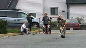 A bunch of young kids demonstrate good team work and passing while playing road hockey in the middle of summer.