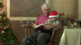 A proud grandfather reads the Christmas story to his adorable Asian grandson.